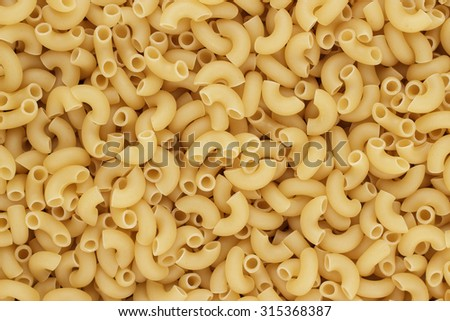 close-up of dry uncooked macaroni pasta on the table  - stock photo