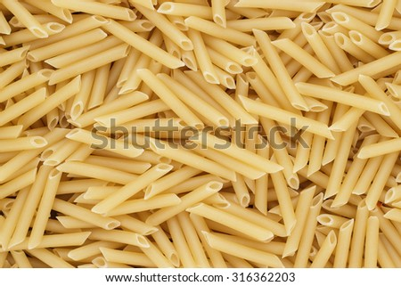 close-up of dry uncooked penne lisce pasta on the table texture background - stock photo
