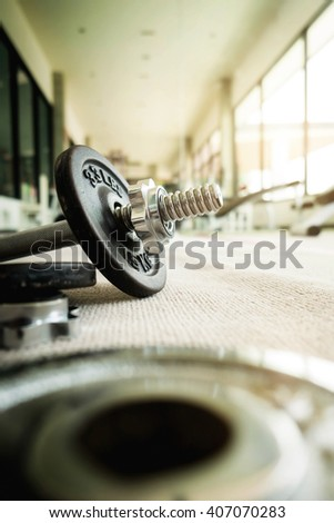 Close up of dumbbell exercise weights on the floor at fitness gym vintage tone. - stock photo