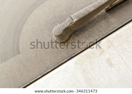 Close-up of dust covered car windscreen wipers which needs a car-wash to remove the dirt - stock photo