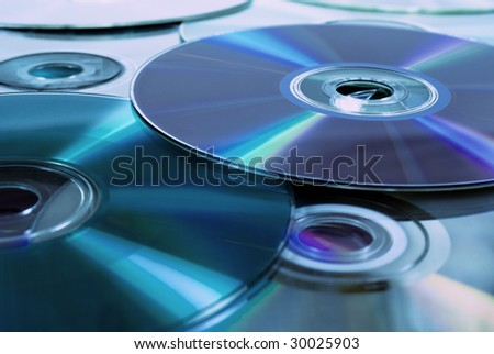 Close up of dvd discs as background, rainbow reflection, blue light - stock photo