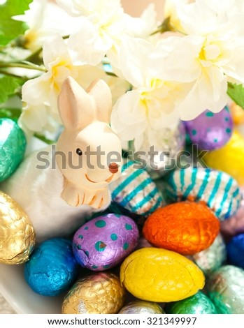 Close up of Easter bunny, flowers and small chocolate Easter eggs in the basket. - stock photo