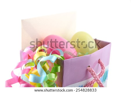 Close up of Easter gift bag with card, eggs, and ribbon. - stock photo