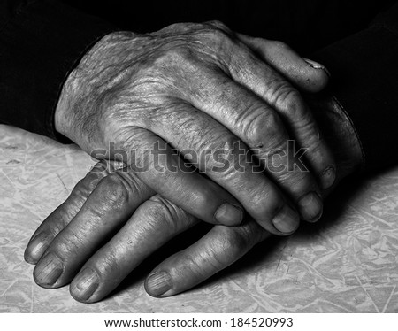 close up of elderly male hands on wooden table - stock photo