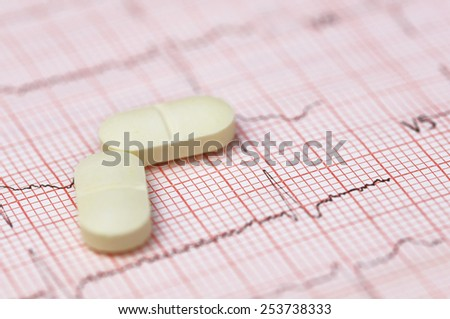 Close up of electrocardiograph with pills - stock photo