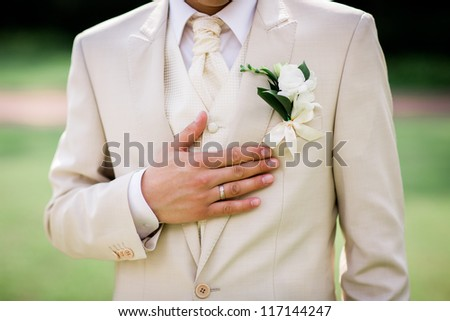 Close-up of elegance groom hands with ring, and cufflink - stock photo