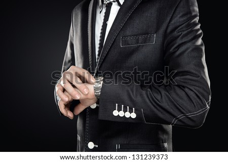 Close up of elegant man wearing suit checking the time isolated on gray background with copy space - stock photo