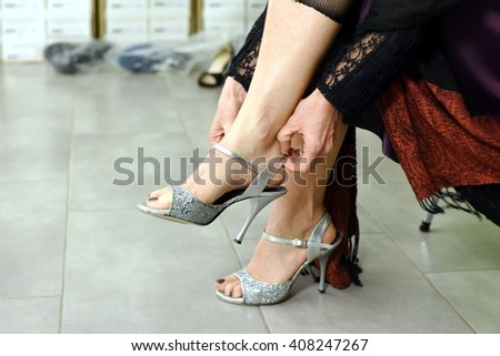 Close up of elegant woman trying silver shoes sitting in a shop - stock photo