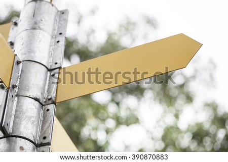 Close-up of empty directional sign against blue sky with clouds. - stock photo