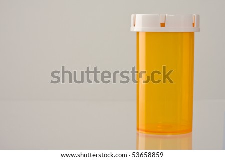 Close up of empty medicine bottle with reflection.  Lots of copy space. Concept of healthcare and medical topics. - stock photo