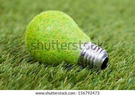 Close-up Of Energy Saving Bulb On Green Grass - stock photo