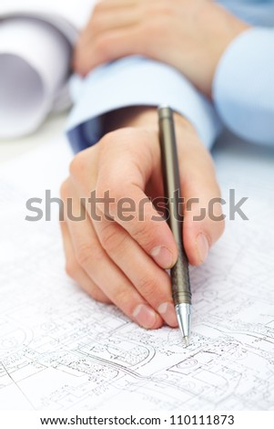 Close-up of engineer hand with pen over blueprint with sketches of projects - stock photo