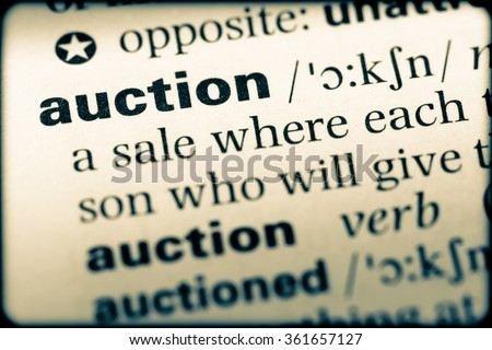 Close up of English dictionary page with word auction - stock photo