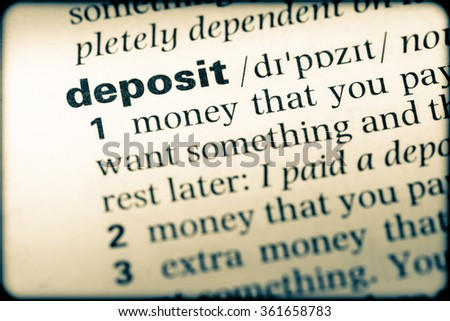 Close up of English dictionary page with word deposit - stock photo