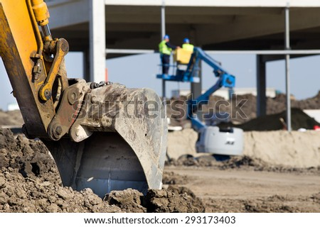 Close up of excavator bucket grounded on construction site and workers on cherry picker in background - stock photo