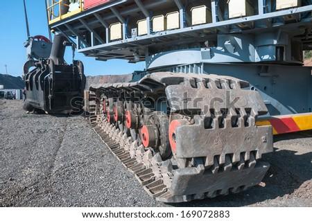 close up of  excavator crawler track  extracting iron ore in opencast mine - stock photo