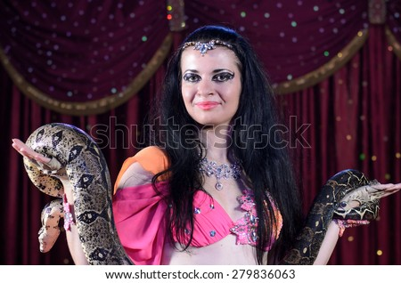 Close Up of Exotic Female Snake Dancer with Dark Hair Holding Large Snake in Both Hands Standing on Stage - stock photo