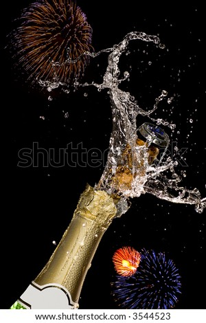 Close-up of explosion of champagne bottle cork with fireworks bursts in backgrounds - stock photo