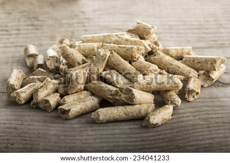 Close up of extruded wood pellets on wooden background - stock photo