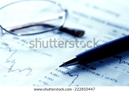 close-up of eyeglasses and pen over financial market graphs - stock photo