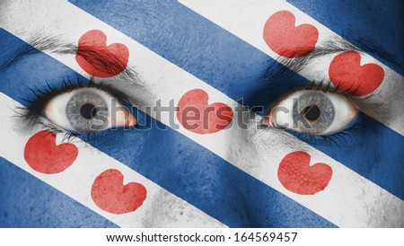 Close up of eyes. Painted face with flag of Friesland - stock photo
