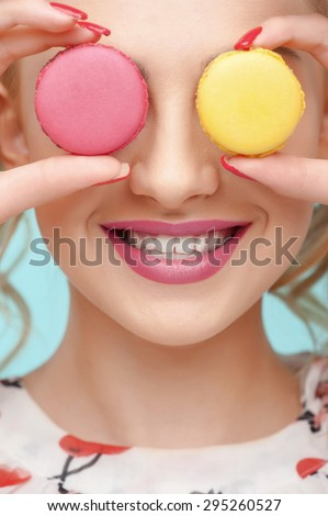 Close up of face of cheerful woman covering her eyes with brownies. She is laughing with joy - stock photo