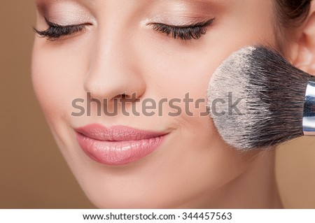 Close up of face of young woman getting powder on her cheek with a brush. She is smiling. Her eyes are closed - stock photo