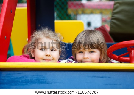 Close up of faces of two happy playful girls sitting in car toy on playground - stock photo