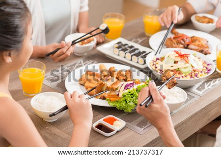 Close-up of family eating traditional Vietnamese food - stock photo