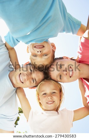 Close Up Of Family Group Looking Down Into Camera In Park - stock photo