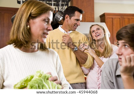 Close-up of family with two teenage children in kitchen - stock photo