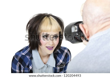 Close-up of fashion photographer with model posing in studio - stock photo