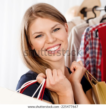 Close up of fashionable woman buyer with shopping bags. Young pretty Caucasian female purchasing clothes in small boutique.  - stock photo