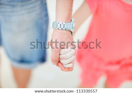 Close up of father and daughter holding hands at beach - stock photo