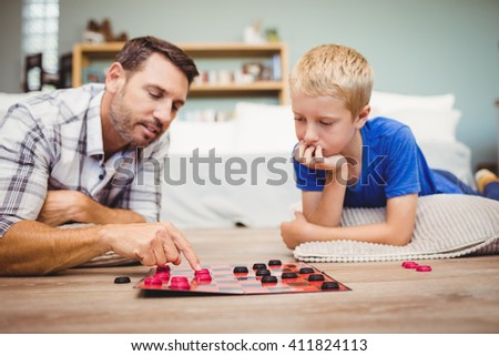 Close-up of father and son playing checker game while lying on floor at home - stock photo