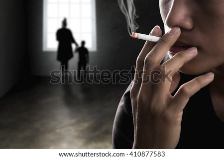 Close up of father hand smoke a cigarette with mother and son at background. Concept of tobacco day. - stock photo