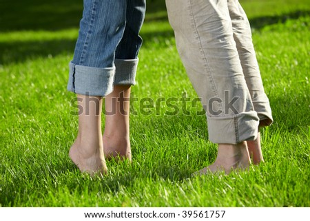 Close up of feet of a couple on a summer meadow - stock photo