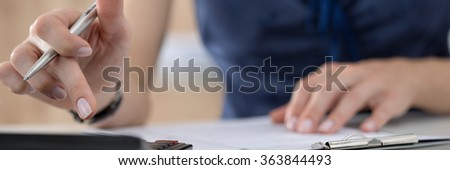 Close up of female accountant or banker making calculations. Savings, finances and economy concept. Letter box format - stock photo