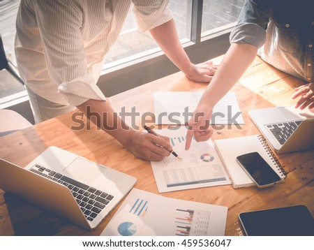 Close-up of female and male hands pointing at turnover graph while discussing it on wooden desk in office. group concept. Vintage filter effect. - stock photo