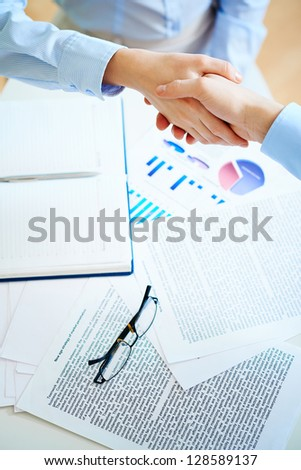 Close-up of female and male handshaking over workplace with business documents - stock photo