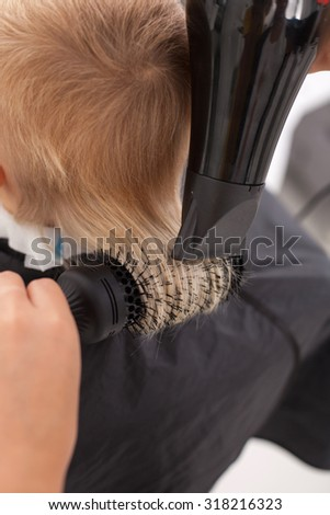 Close up of female arms of hairstylist. The woman is drying hair of boy with hair-drier and comb. The child is sitting in chair. Focus on his back - stock photo