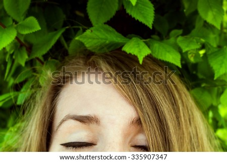 close up of female closed eyes with foliage above her head. soft focus. - stock photo