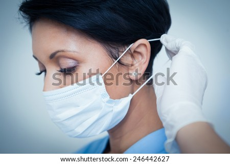 Close up of female dentist wearing surgical mask - stock photo