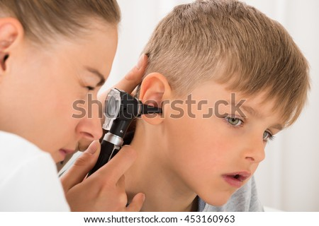 Close-up Of Female Doctor Examining Boy's Ear With An Otoscope - stock photo