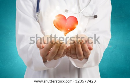 Close up of female doctor holding heart in hands - stock photo