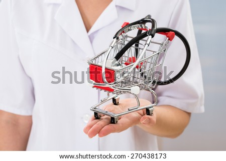 Close-up Of Female Doctor Holding Small Shopping Cart With Stethoscope - stock photo
