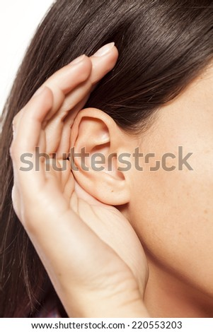 close-up of female ear and palm behind him - stock photo