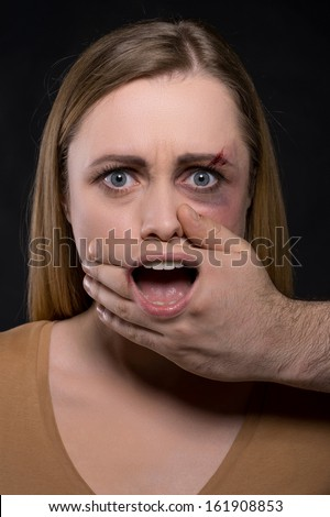 Close up of Female face with covered mouth by male hand and mouth seen through the hand. Concept of woman being attacked and made to be silent when need to shout   - stock photo