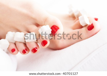 Close-up of female feet with red polished nails - stock photo