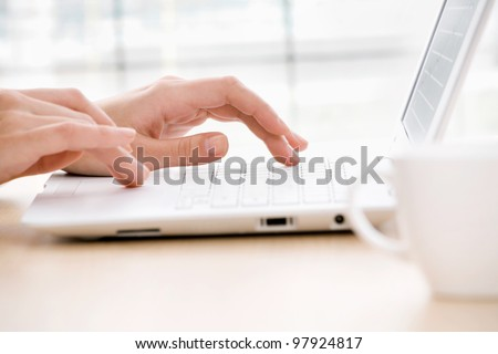 Close-up of female fingers typing a business document on the laptop - stock photo